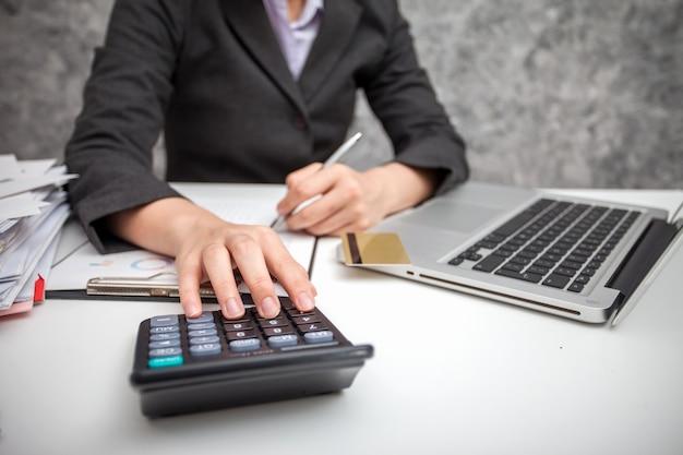 Geschäftsfrauen, die taschenrechner am arbeiten mit finanzberichten verwenden.