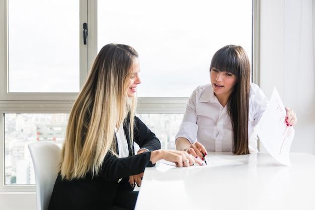 Geschäftsfrauen, die unternehmensplan am arbeitsplatz im büro besprechen