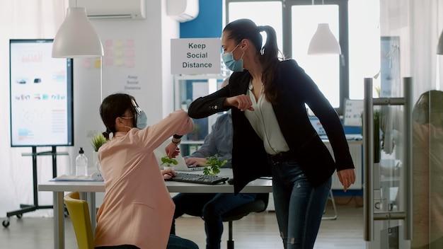 Geschäftsfrauen, die während des ausbruchs des coronavirus den ellbogen berühren, während sie auf dem computer tippen, tragen gesichtsschutzmasken, um eine infektion mit viruserkrankungen zu vermeiden. personengesellschaft, die soziale distanzierung respektiert