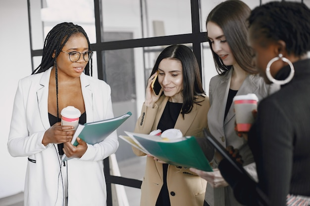 Geschäftsfrauen, die während einer kaffeepause im flur des großen unternehmens in der nähe des schreibtisches sprechen