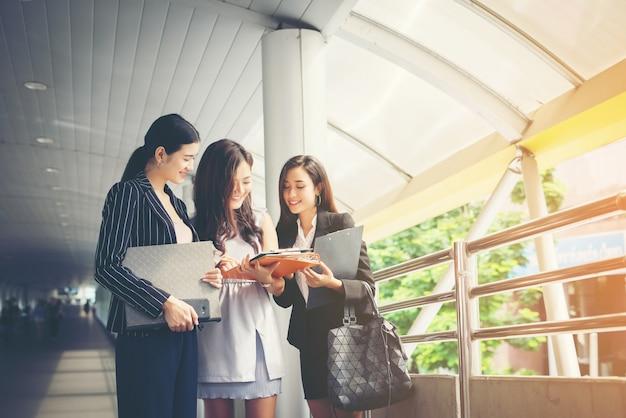 Geschäftsfrauen diskutieren über papierkram zusammen gegen geländer. geschäftsleute konzept.