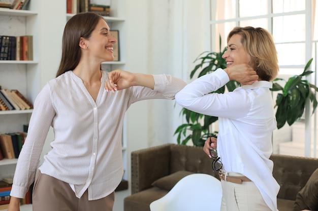 Geschäftsfrauen halten wegen der covid-19-infektion abstand und begrüßen sich mit den ellbogen.
