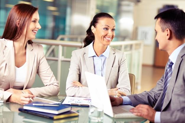Geschäftsfrauen hören und im gespräch mit ihren arbeitskollegen