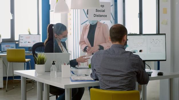 Geschäftsfrauen mit medizinischen gesichtsmasken, die auf finanzdiagramme schauen, die am schreibtisch im startup-büro stehen. mitarbeiter halten soziale distanz ein, um eine infektion mit dem coronavirus während einer epidemie zu vermeiden