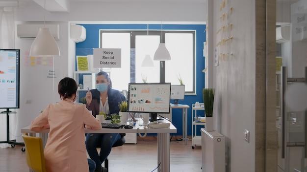 Geschäftsfrauen mit medizinischen gesichtsmasken, die über managementstatistiken sprechen, die am schreibtisch in einem neuen normalen firmenbüro arbeiten. das team hält soziale distanzierung ein, um eine infektion mit dem coronavirus zu vermeiden