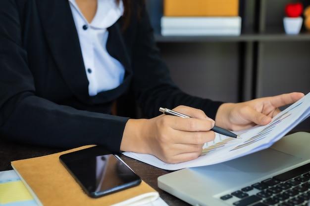 Geschäftsfrauen nahaufnahmehand mit papierschreiben am diagramm, unter verwendung des computer-notebook-laptops und des smartphones, marketinggeschäft für erfolgskonzept.