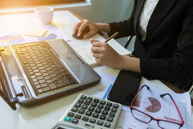 Geschäftsfrauen-nahaufnahmehand mit papierschreiben am diagramm