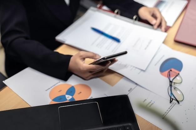 Geschäftsfrauen-nahaufnahmehand mit papierschreiben am diagramm.