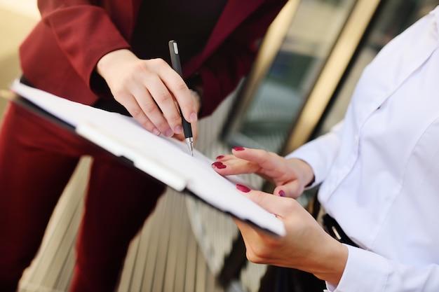 Geschäftsfrauen unterzeichnen einen vertrag oder dokumente