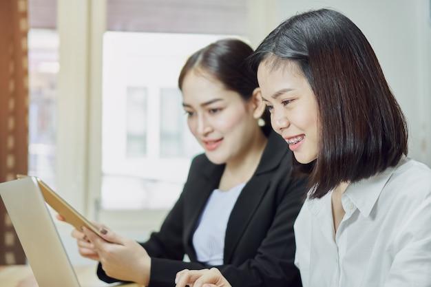 Geschäftsfrauen verwenden laptops und smartphones, um im büro zu arbeiten.