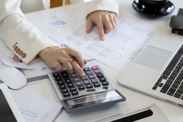 Geschäftsfrauen verwenden taschenrechner, um die ausgaben auf dem schreibtisch zu berechnen