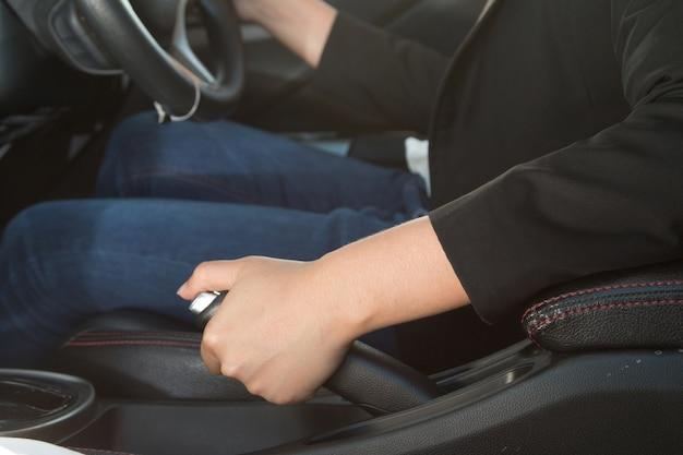 Geschäftsfraufahrer, der die handbremse im auto, im autohintergrund zieht.