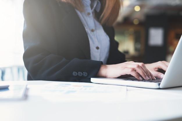 Geschäftsfrauhände, die auf laptoptastatur schreiben.