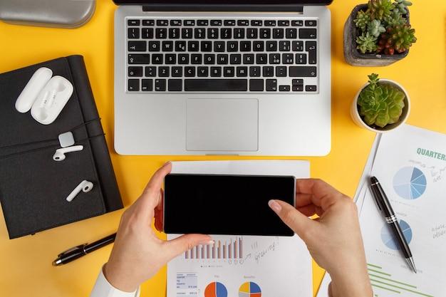Geschäftsfrauhände, die handy in der nähe von laptop halten