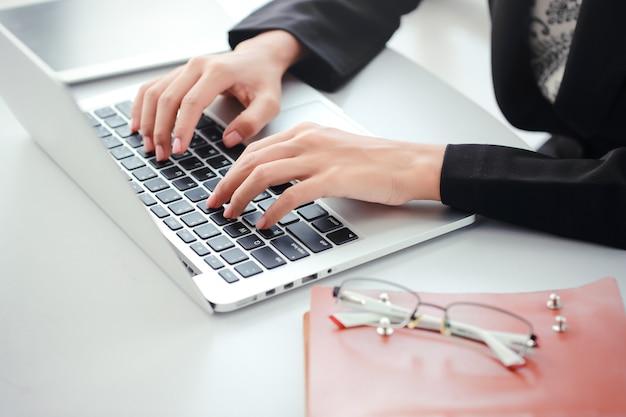 Geschäftsfrauhände mit gläsern unter verwendung des computers