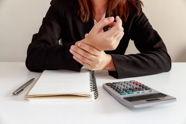 Geschäftsfrauhände schmerzen auf schreibtischbüro-syndrom mit notizbuch und taschenrechner.