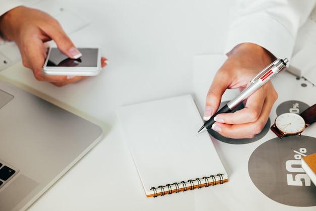 Geschäftsfrauhände unter verwendung der smartphones und auf papierblatt mit leerstellebildschirmanzeige notieren