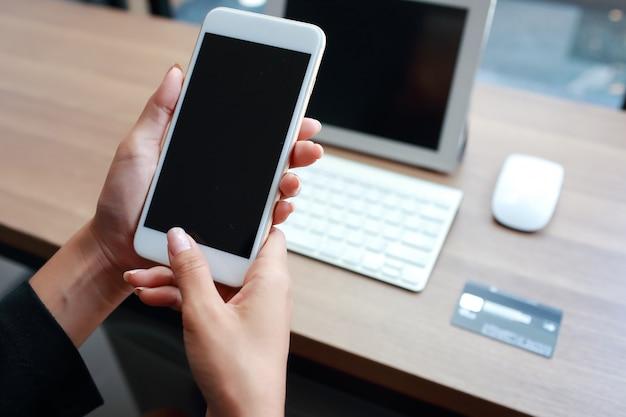 Geschäftsfrauhände unter verwendung der tabelle und des handys