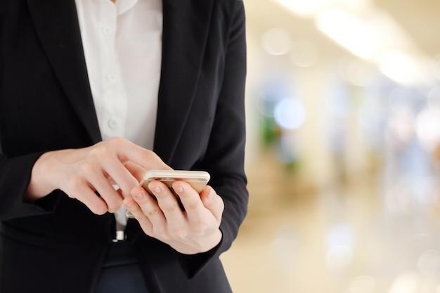Geschäftsfrauhände unter verwendung des intelligenten telefons über unschärfebüro mit hellem hintergrund bokeh, fahne, geschäft am telefon