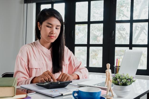 Geschäftsfrauhand, die mit finanzdaten und taschenrechner auf weißem schreibtisch herein modern weg arbeitet