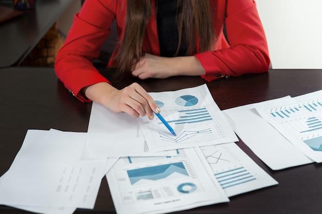 Geschäftsfrauhand, die mit geschäftsdiagramm oder analysediagramm arbeitet. geschäftsteamanalyse und strategiekonzept hautnah.