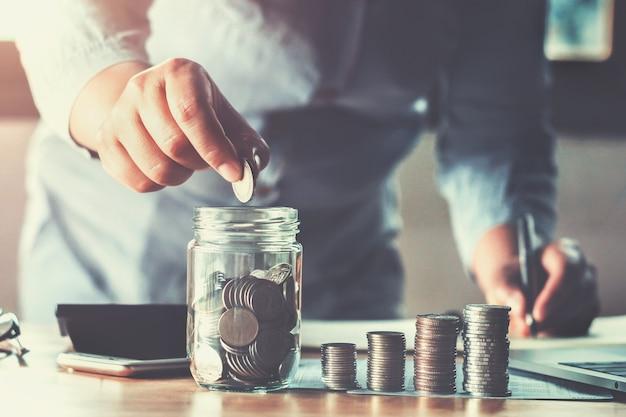 Geschäftsfrauhand, die münzen hält, die in glas setzen.