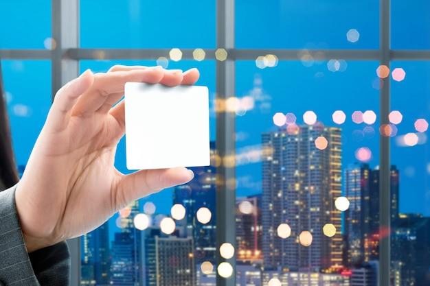Geschäftsfrauhand, die weiße leere karte auf dem büro zeigt