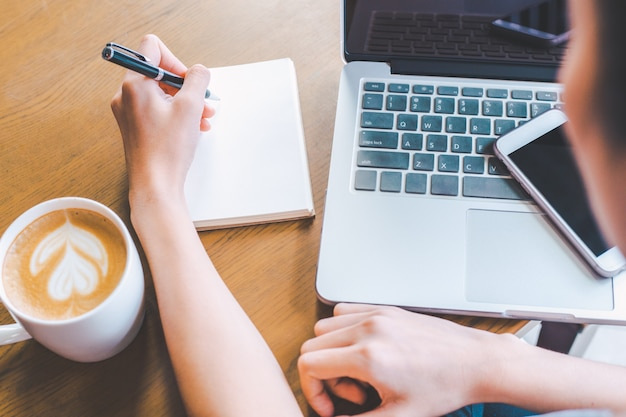 Geschäftsfrauhand schreibt auf einen notizblock mit einem stift.
