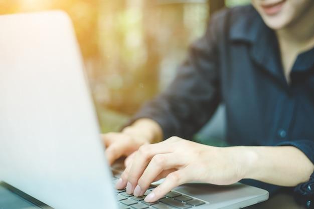 Geschäftsfrauhandarbeitslaptop-computer im büro