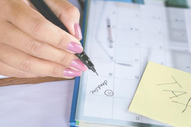 Geschäftsfrauhandschrift auf kalenderabschlußwort für steuerzeit