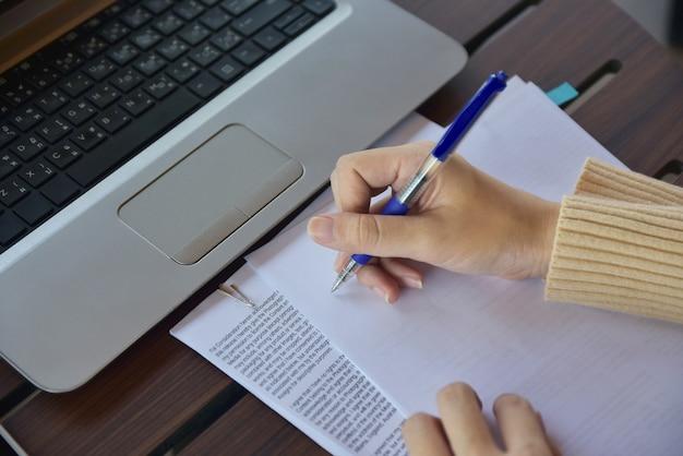 Geschäftsfrauholdingfeder und schreiben auf papier