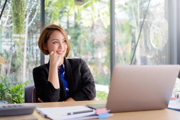 Geschäftsfraulächeln auf gesicht mit dem denken der kreativen idee.