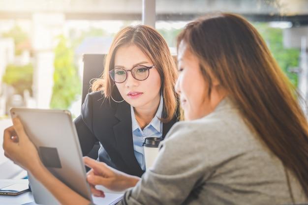 Geschäftsfrauleute, die geschäftsplanung oder finanzbericht von der tablette für junge darstellen