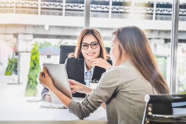 Geschäftsfrauleute, die geschäftsplanung und finanzbericht von der tablette für ceo darstellen