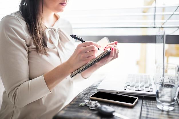 Geschäftsfrauschreiben auf tagebuch