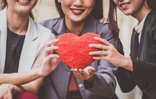 Geschäftsfrauteam, das einem kunden ein rotes herz gibt