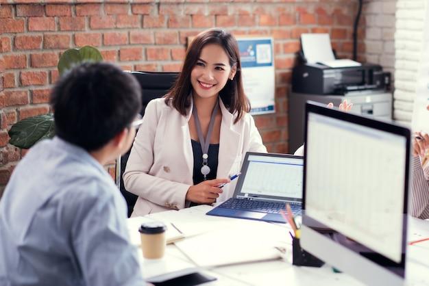 Geschäftsfrautrainer, der defocused gruppe von personen erklärt