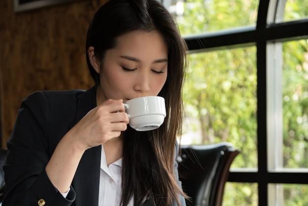 Geschäftsfrautrinkbecher kaffee morgens am shop.