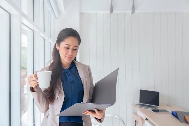 Geschäftsfrautrinkbecher kaffee und stellung an einem fenster im büro