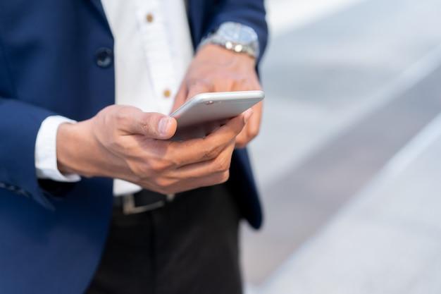Geschäftsführergeschäftsmann, der smartphone zum arbeiten, zur technologie und zum geschäftskonzept hält