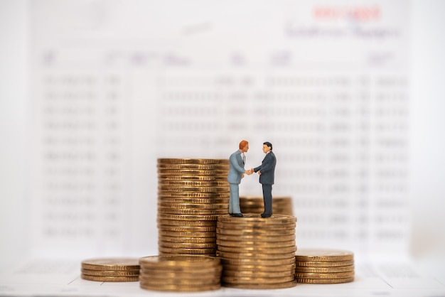 Geschäftsgeld sparen und arbeitskonzept. zwei geschäftsmann miniaturfigur menschen erstechen und hand schütteln auf stapel goldmünzen auf bank sparbuch.