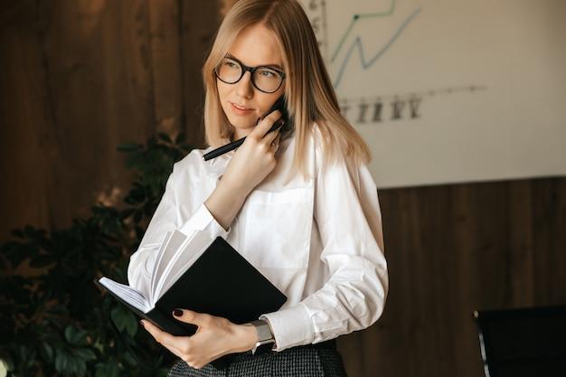 Geschäftsgespräch am telefon im büro während der arbeitszeit, spricht eine geschäftsfrau auf einem smartphone.