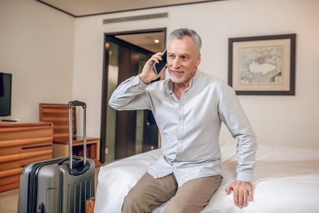 Geschäftsgespräch. grauhaariger geschäftsmann mittleren alters, der am telefon spricht und beteiligt aussieht
