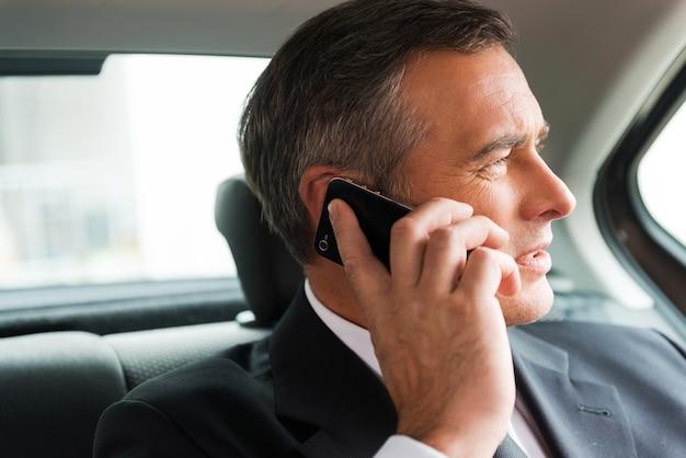 Geschäftsgespräch im auto. selbstbewusster reifer geschäftsmann, der mit dem handy spricht und wegschaut, während er auf dem rücksitz eines autos sitzt