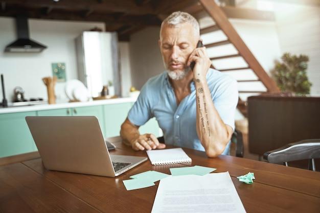 Geschäftsgespräch kaukasischer mann mittleren alters, der am tisch sitzt und online telefoniert