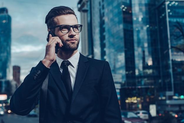 Geschäftsgespräch. nachtbild eines selbstbewussten jungen mannes im vollen anzug