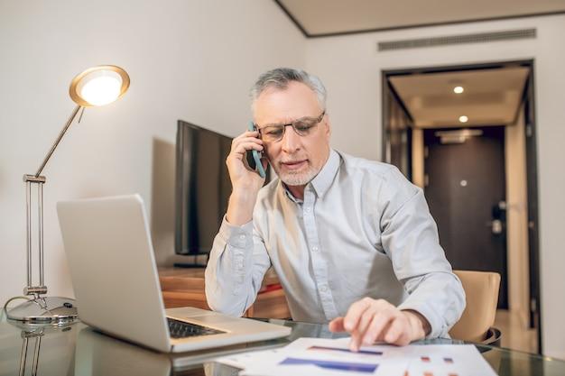 Geschäftsgespräch. reifer mann, der am telefon spricht und involviert aussieht