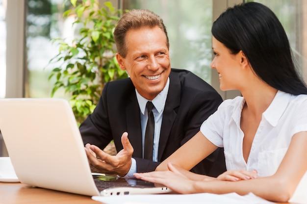 Geschäftsgespräch. zwei geschäftsleute in abendgarderobe diskutieren etwas und lächeln, während beide draußen am tisch sitzen