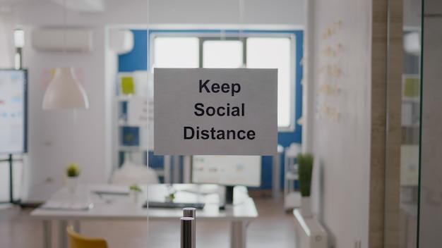 Geschäftsglasinnenbüro mit sozialem abstandsschild an der wand. moderne büroräume mit niemandem darin während der globalen pandemie, coronavirus-krise