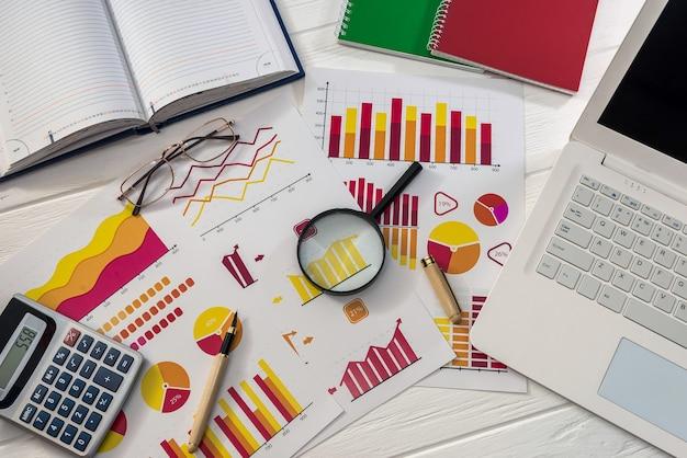 Geschäftsgraphen mit laptop und lupe am schreibtisch